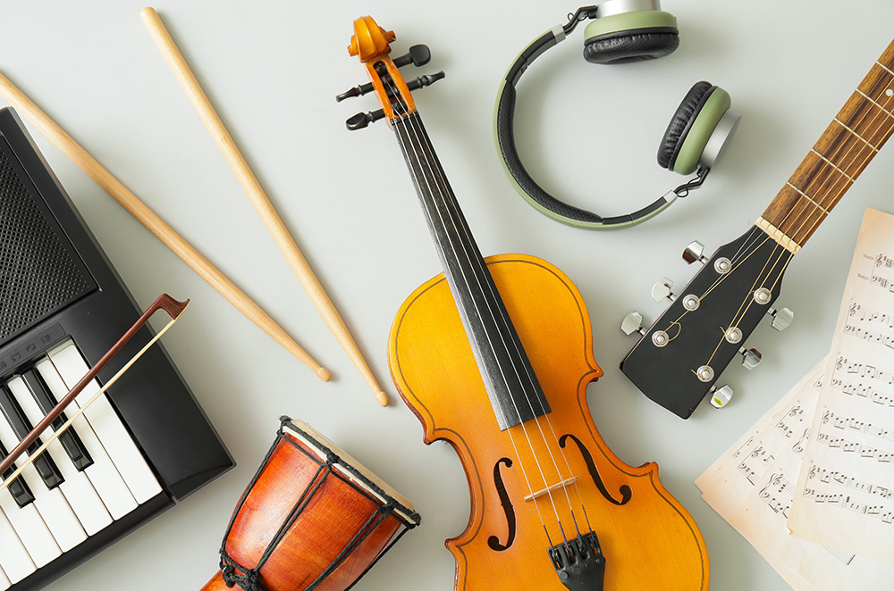 Different musical instruments and music notes on light backgroun