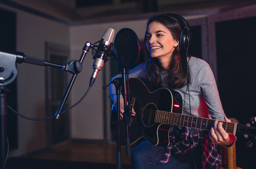 Woman recording a song in a professional music studio